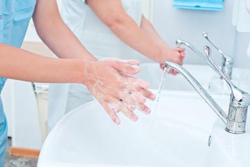 Surgeon washing hands before operation