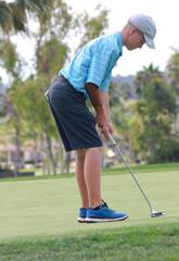 Male teen golfer putting on green 1