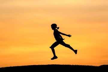 Girl leaps during sunset.