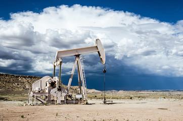 Erdölförderung in der Wüste vor dunklen Gewitterwolken