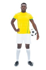Football player in yellow standing with the ball