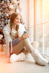 Beautiful young woman drinking tea at the Christmas tree. Beauti