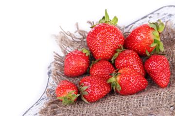 Ripe sweet strawberries on sackcloth napkin isolated on white