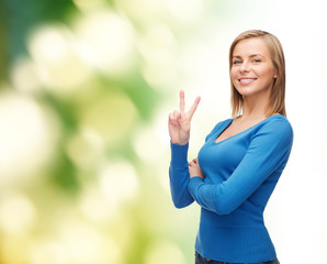 smiling teenage girl showing v-sign with hand