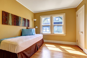 Simple bedroom with single bed in colorful bedding
