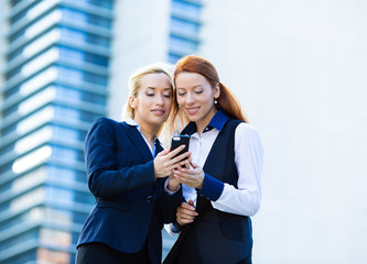 Happy business women reading e-mail on mobile smart phone