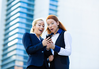 Surprised business women looking at smart phone, good news