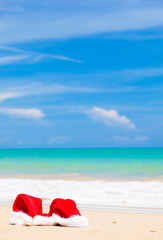 two santa hats lying on tropical sand beach. party. christmas.