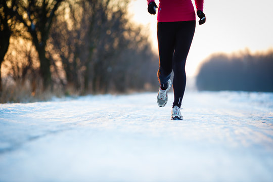 Winter running - Young woman running outdoors on a cold  day