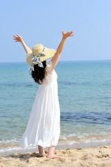 ビーチで麦わら帽子と白いドレスを着た女性