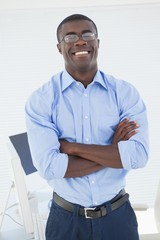 Happy businessman standing with arms crossed
