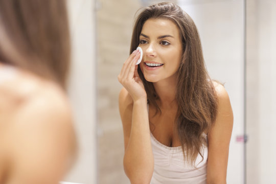 Beautiful brunette woman removing makeup from her face