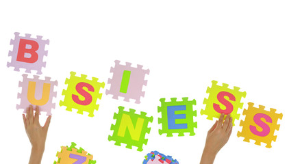 """Hands forming word """"Business"""" with jigsaw puzzle pieces isolated"""