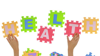 """Hands forming word """"Health"""" with jigsaw puzzle pieces isolated"""