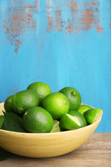 Fresh juicy limes in bowl on blue wooden background