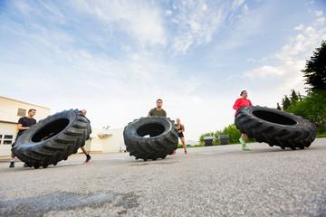 Athletes Doing Tire-Flip Exercise