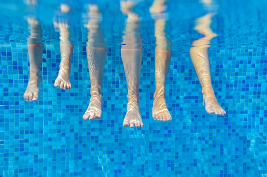 Funny underwater family legs in swimming pool on vacation