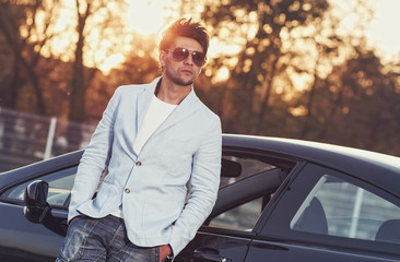 Trendy handsome young man leaning on his car