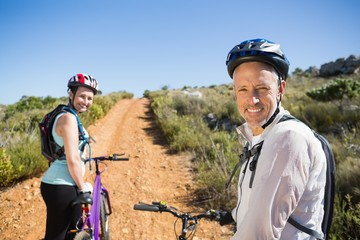 Active couple cycling on country terrain together