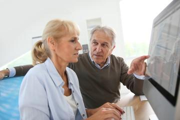 Senior people in office working on desktop computer