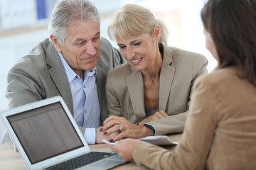 Senior couple meeting financial adviser in office