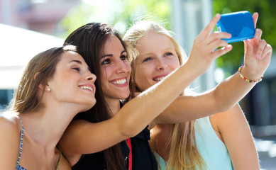 Group of friends taking selfie in the street.