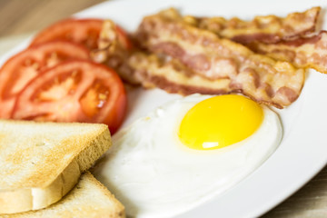 English Breakfast With Fried Egg, Bacon, Toast And Tomatoes