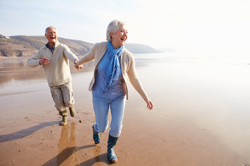 Senior Couple Running Along Winter Beach