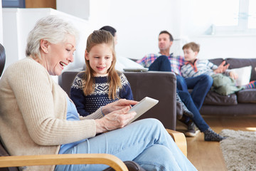 Grandmother And Granddaughter Using Digital Tablet Together