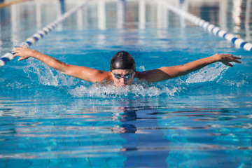 dynamic and fit swimmer in cap breathing performing the butterfl