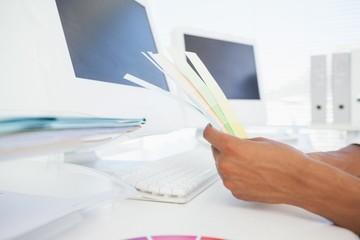 Designer working at desk holding colour samples