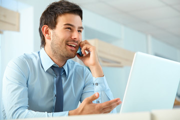 Smiling business man talking on mobile phone in a office