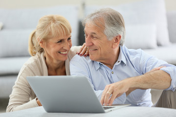 Senior couple websurfing on internet with laptop