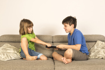 Kids arguing for playing with a digital tablet on a sofa.