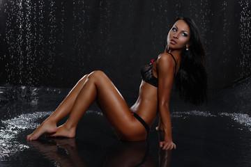 beautiful sexy woman in water studio in black background