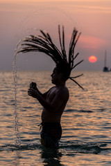 KOH LIPE, THAILAND - MARCH 23, 2013: Young Rastafari playing wit