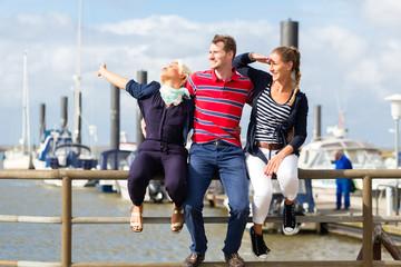 Freunde trinken Bier am Jachthafen Kai