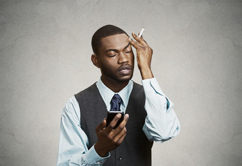 Upset, stressed businessman having bad headache, holding mobile