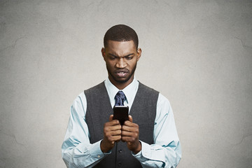 Angry young executive holding smart phone, reading e-mail
