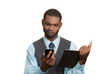 Skeptical man looking at phone holding book, unhappy