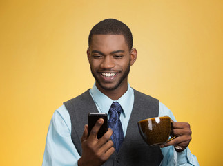Businessman reading news on mobile, drinking tea