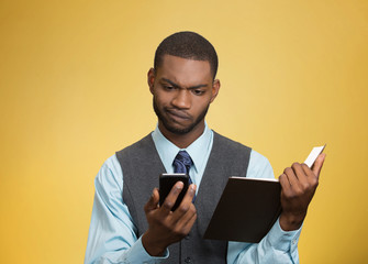 Portrait skeptical man looking at phone holding book
