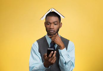 Man holding mobile, book over head isolated on yellow background