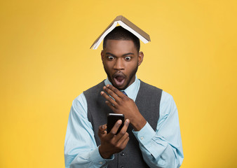 Shocked man holding smart phone, reading news, book over head