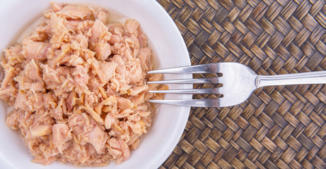 Pieces of canned tuna in a white bowl with a fork on wicker