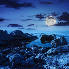 calm sea wave on rocky shore at night