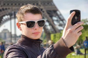 A young man in Paris take a selfie in front of the Eiffel Tower