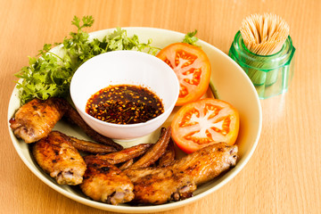Grilled chicken wings on dish.