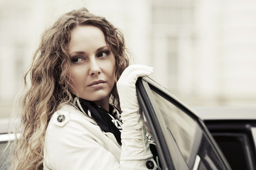 Fashion beautiful woman with long curly hairs at the car
