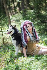 Indian girl playing with husky dog. War bonnet